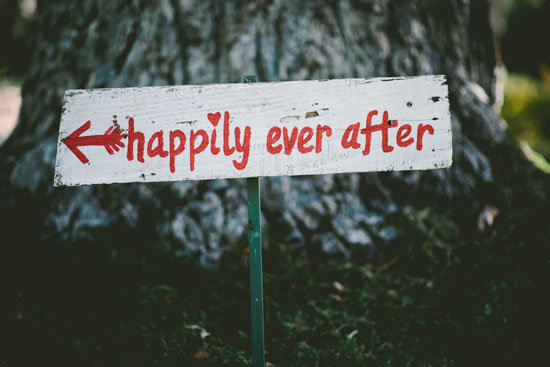 Sign board of Happily ever after written with an arrow in red color on white board, fixed on ground near a tree - AAAF
