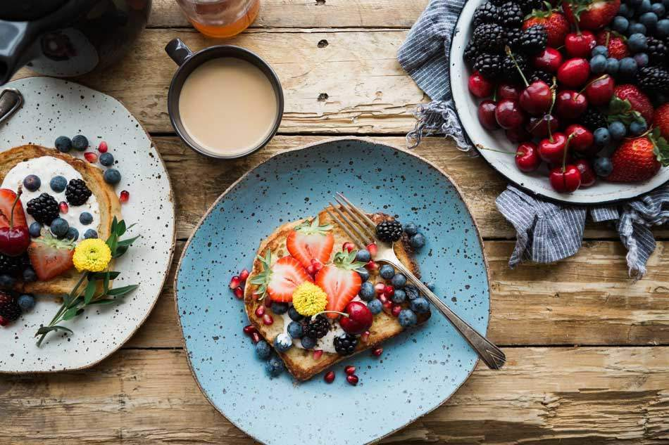 Strawberry, Blueberry, Pomegranate, Cherry on a Bread slice with fork on blue plate. Tea in a cup on wooden table. AAAF