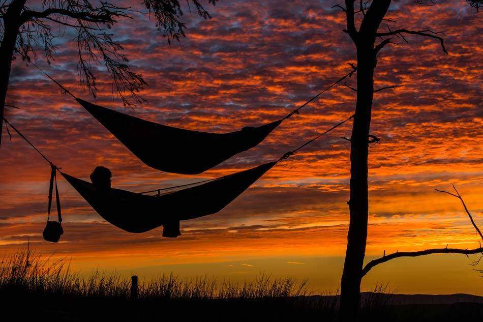 Person lying on one of the two hanging hammocks tied to trees under red sky at sunset. AAAF
