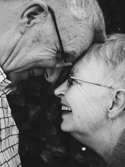 An Old couple laughing with their foreheads touching each other, filled with joy and peace - AAAF