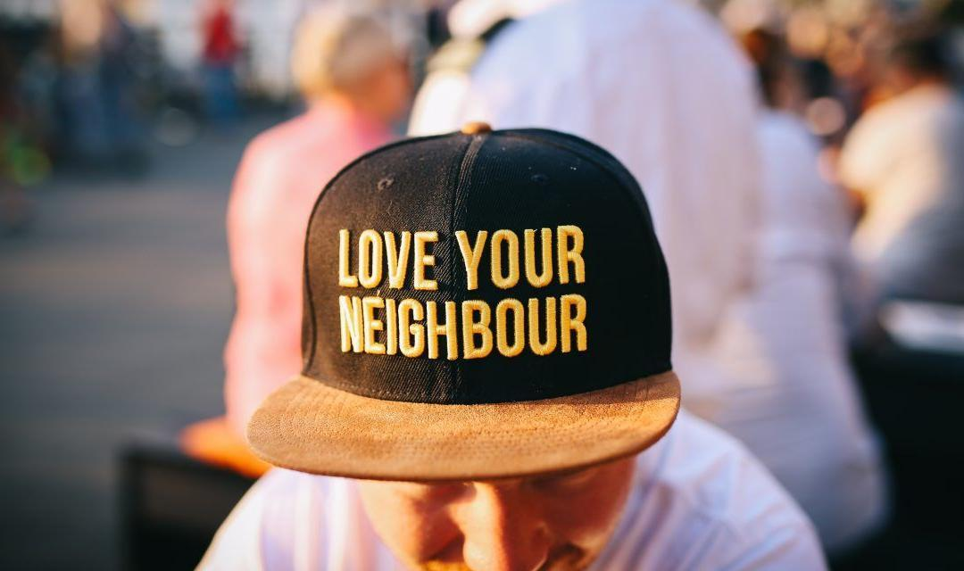 Love your neighbour cap in black and orange as we answer how does one become a Seventh Day Adventist - AAAF