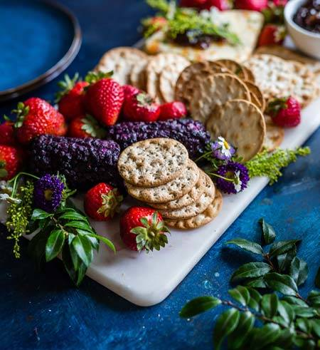 Strawberry & biscuits with blue flowers & green leaves on a white cutting board on blue tablecloth - AAAF