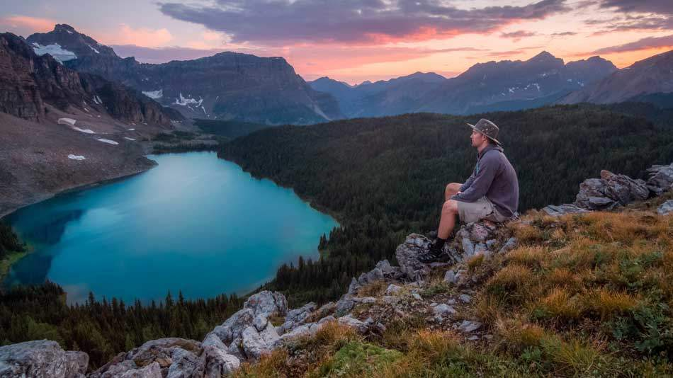 A man sitting on rocks near a lake next to a forest, looking at the mountain range across - AAAF