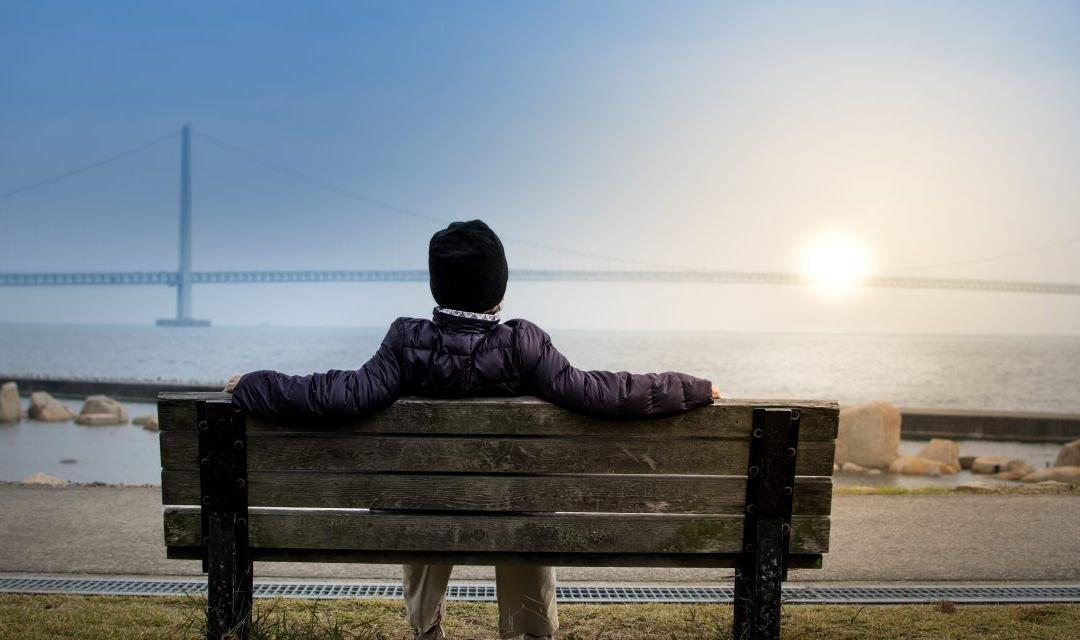 Person sitting on a wodden bench near waterbody, looking at sunset / sunrise across the bridge - AAAF