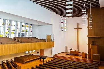 Empty Church wooden pews in ground floor and balcony with a large cross in front - AAAF