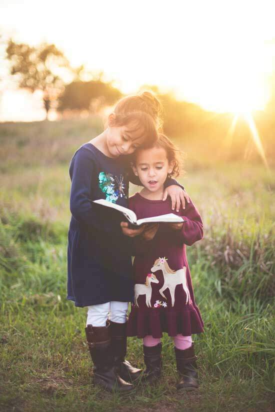 Elder sister reading the Bible for the younger one, embracing her with one arm, outdoors as sun shines on them