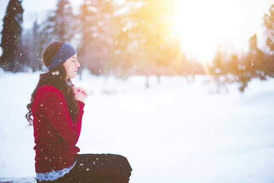 Woman in red praying in snow & sunlight as she learns to know His voice & love to hear Him while communing with God in prayer