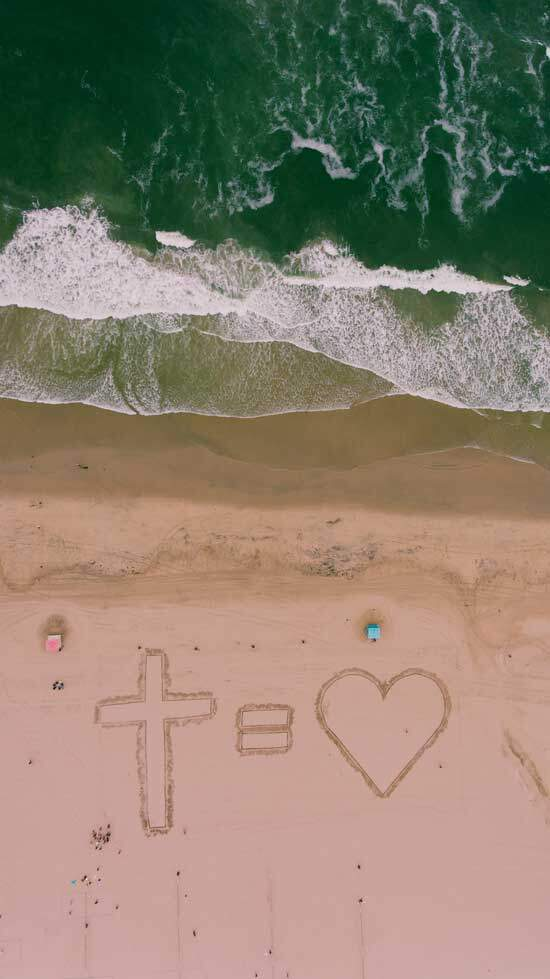 Cross equals Love drawn on sand at the beach, as we are drawn back in love to God through His Son Jesus Christ