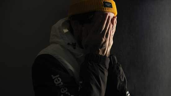 A person hiding his face with his hands, in shame and fear, feeling unworthy of forgiveness