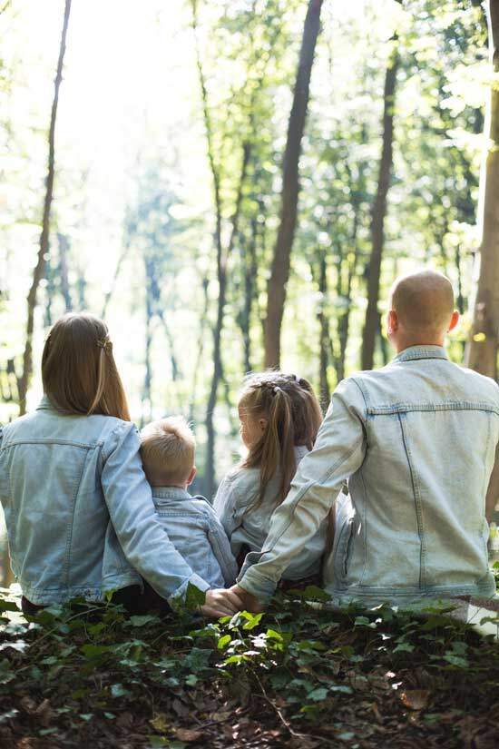 Father, mother, son & daughter sitting on the ground in a forest. Parents holding hands together in love & commitment
