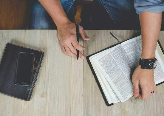 Man studying the word Trinity as it does not appear in the Bible but the concept and explanation comes up in several places