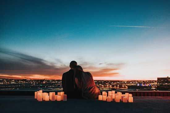 Husband & Wife in love, sitting together with candles around them, looking at the wide expanse of city lights & blue sky