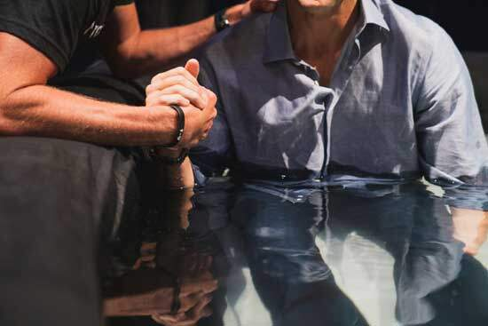 Man being baptized by immersion as Adventists believe that when a person accepts Jesus, he is completely forgiven of his sins