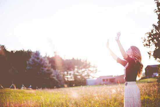 Woman outdoors with hands raised, giving Praise & Thanks to God for the victory over sin & evil and claiming it for herself