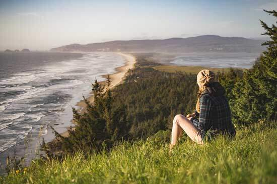 Woman sitting on the grass, on a hill, near a seashore, observing the natural landscape & growing in relationship with Jesus
