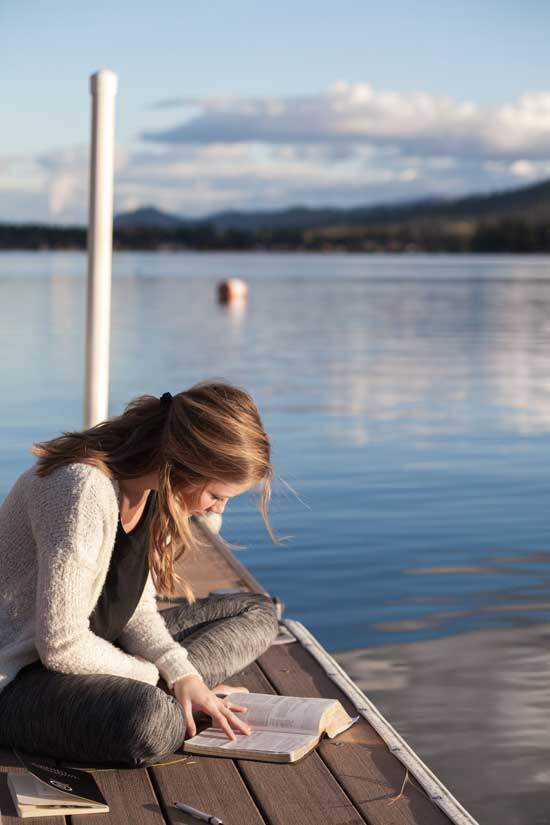 Woman sitting at the shore of a lake, daily feeding on the Word of God, the Bible