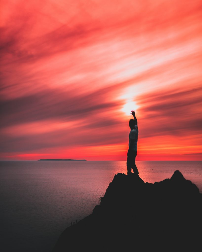 A person standing on a rock beside a sea, holding his right hand up towards the sun shining in a red sky - AAAF