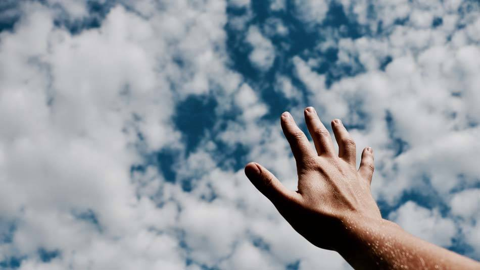 Hand stretched wit open palm towards the sky filled with white clouds, reaching out to God in hope and faith - AAAF