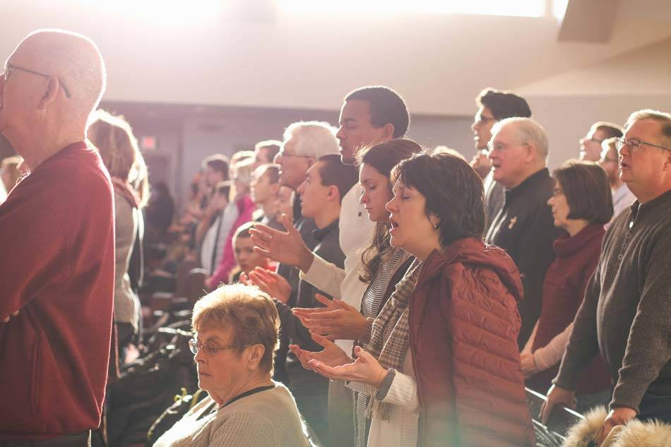 Church Congregation standing from their pews & singing Amen during worship with closed eyes and open hands - AAAF