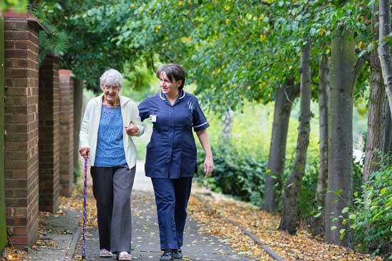 Elderly woman walking with nurse as Adventist Health Studies examine the relationship between lifestyle, diet & diseases